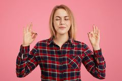 Positive concentrated female keeps hands in mudra gesture, closes eyes, tries to relax for minute, imagines something pleasant, ke. Eps eyes closed, isolated royalty free stock photo