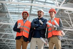 Positive confident engineers are attending construction. Visit object. Low angle portrait of cheerful young architects are standing in safety-helmets and looking stock images