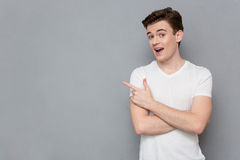 Positive confident young man poiting away in copyspace. Positive content happy smiling confident young man in white t-shirt poiting away in copyspace Stock Images