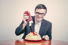 Positive consumerism. Concept. Happy businessman pouring ketchup on large dish of pasta royalty free stock photos
