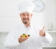 Positive cook with greek salad Royalty Free Stock Images
