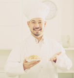 Positive cook with porridge Royalty Free Stock Photo