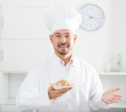 Positive cook with porridge Royalty Free Stock Photography