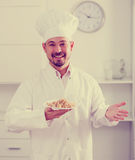 Positive cook with porridge Royalty Free Stock Images
