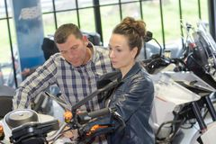Positive couple buying motorbike in workshop Royalty Free Stock Photography