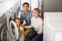 Positive couple buying washing machine Stock Photos