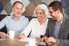 Positive couple cooperating with sales manager Royalty Free Stock Image