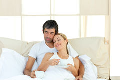 Positive couple drinking coffee lying in the bed Royalty Free Stock Images