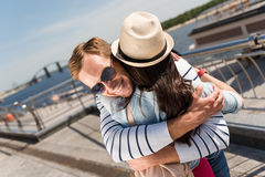 Positive couple embracing. Show your feelings. Cheerful loving couple smiling and embracing while standing on the dock Stock Images