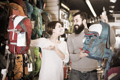 Positive couple examining rucksacks in sports equipment store Royalty Free Stock Images
