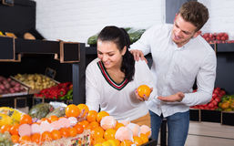 Positive couple examining various fruits Royalty Free Stock Photos