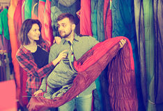 Positive couple examining various sleeping bags Royalty Free Stock Images