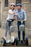 Positive couple going sightseeing by segways Stock Photography