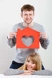 Positive couple with heart house. Stock Photography