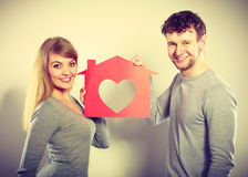 Positive couple with heart house. Stock Photos