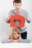 Positive couple with heart house. Royalty Free Stock Photos