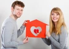 Positive couple with heart house. Stock Photos
