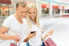 Positive couple holding packages Royalty Free Stock Photos