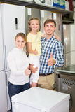 Positive couple with kid choosing microwave Stock Images