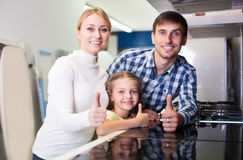 Positive couple with kid choosing microwave Royalty Free Stock Image