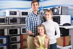 Positive couple with kid in store with electronics Stock Image