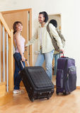 Positive couple with luggage in home going Stock Images