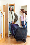 Positive couple with luggage in home going on holiday. Young positive couple with luggage near door going on holiday Royalty Free Stock Photos