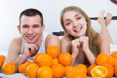 Positive couple lying with orange fruits Royalty Free Stock Image