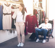 Positive couple purchasing dress and blouse. At clothing shop Royalty Free Stock Photo