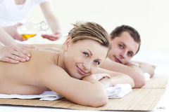 Positive couple receiving a back massage with oil. Positive young couple receiving a back massage with oil in a health spa stock photography