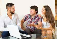 Positive couple and salesman talking. Positive young couple and salesman talking cheerfully about purchase at home stock images