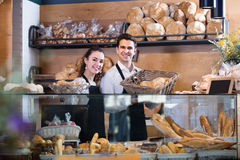 Positive couple selling pastry and loaves Stock Image