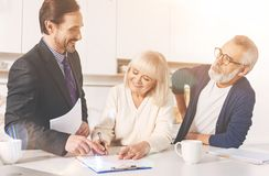 Positive couple signing papers with insurance agent royalty free stock photo