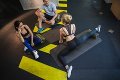 Positive couple is stretching with coach in gym royalty free stock photos