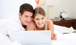 Positive couple surfing on the internet Stock Images