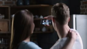 Positive couple taking selfie together at home stock footage