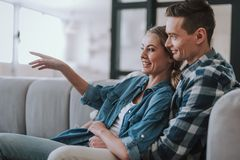 Positive couple watching TV on the sofa and smiling stock image