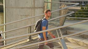 Positive courier walking up the stairs in modern city district, making delivery. Stock footage stock video footage