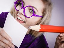 Crazy woman holds big pencil in hand. Positive crazy woman blonde student girl or female teacher, business coach holding huge red pencil and note paper, planning Royalty Free Stock Images