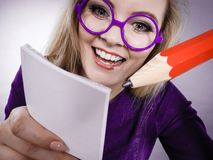 Crazy woman holds big pencil in hand. Positive crazy woman blonde student girl or female teacher, business coach holding huge red pencil and note paper, planning Royalty Free Stock Photography