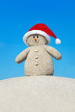 Positive creative sandy Snowman in red Santa hat at beach Royalty Free Stock Images