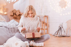 Positive curious woman opening a Christmas box Royalty Free Stock Photography