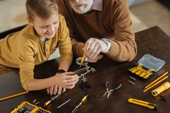 Positive cute boy learning new skills. Personal development. Positive delighted cute boy sitting together with his grandfather and helping him while learning new Royalty Free Stock Photography