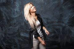 Positive cute cheerful girl with blond hair laughing on a dark b. Ackground. Happy smile mood Stock Photography