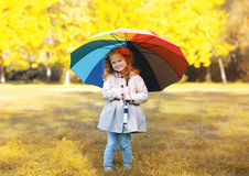 Positive cute child with colorful umbrella in autumn day Royalty Free Stock Images