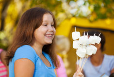 Positive cute girl holds sticks with marshmallow Stock Image