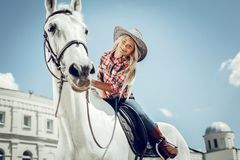 Positive cute girl looking at her horse stock photos