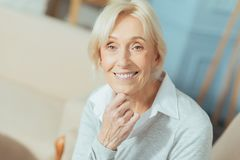 Positive cute pensioner sitting and smiling while having rest royalty free stock photo