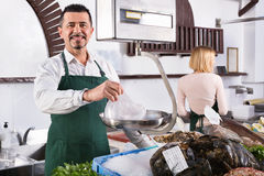 Positive cute shop assistants selling fresh fish Stock Photography
