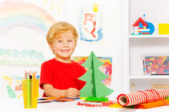 Positive cute small boy holding carton Xmas tree Royalty Free Stock Photos